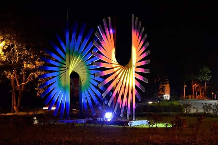 A steel sculpture pictured at night. It appears to be a spiral of beams that fade in color from blue, to orange, to black.