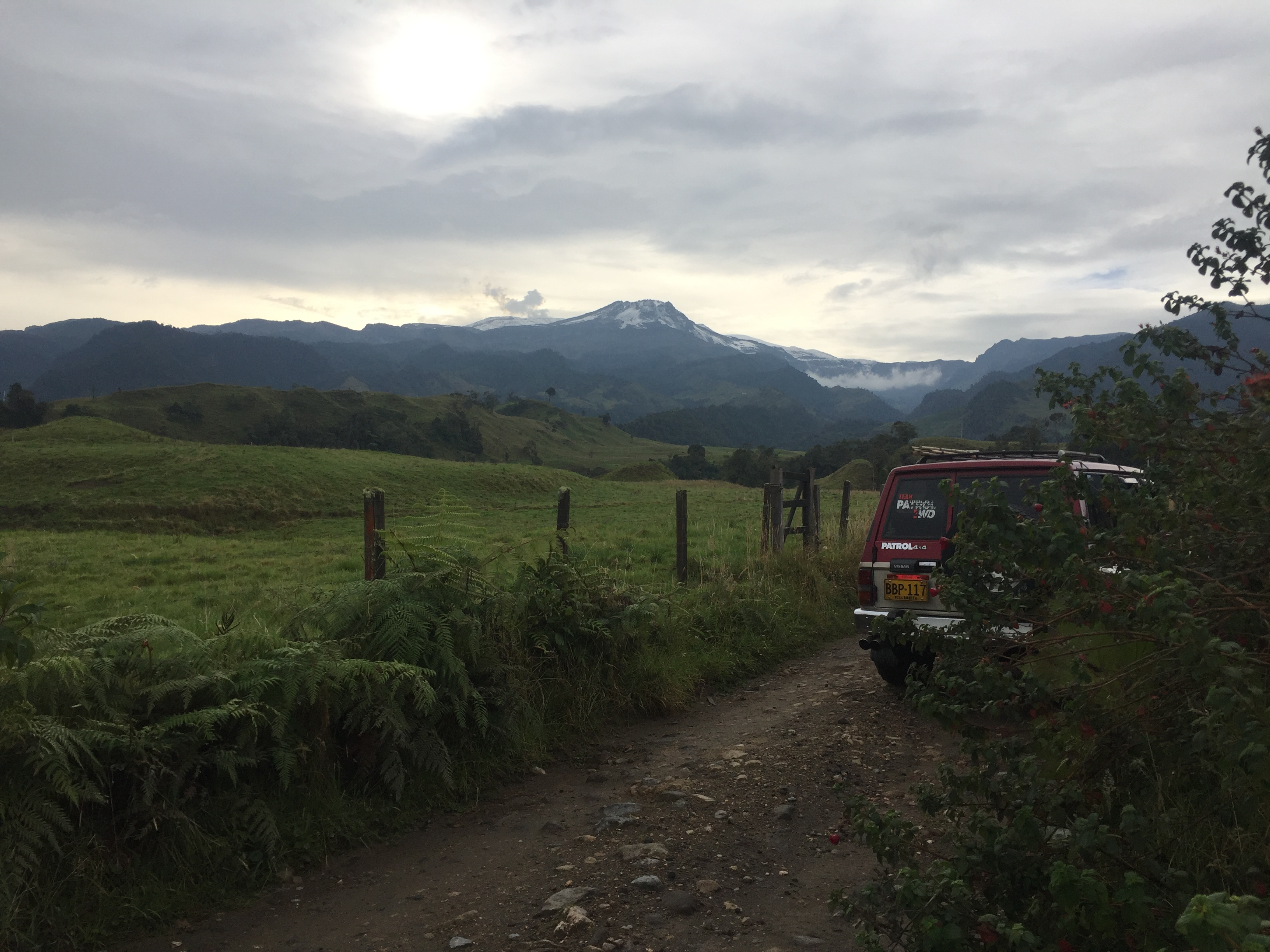 there are many green trees and gassy fields, slowly gaining elevation until it reaches a peak, capped with snow. A range rover is on a dirt road heading toward the mountain.