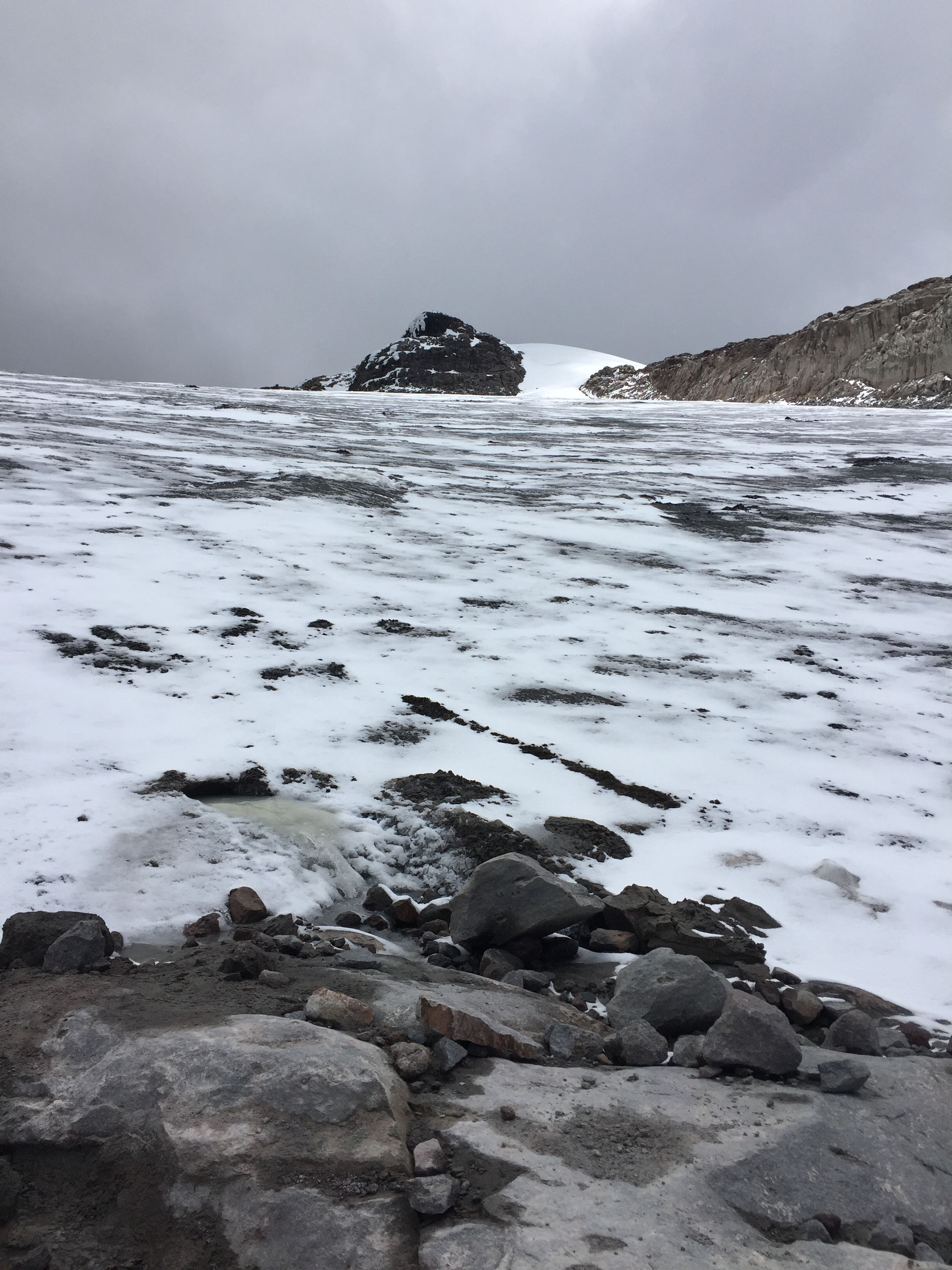 A sharp peak extends out of the glacier at the top of the san isabela nevado. There is still quite a bit of glacier to see, dotted with rocks throughout it.