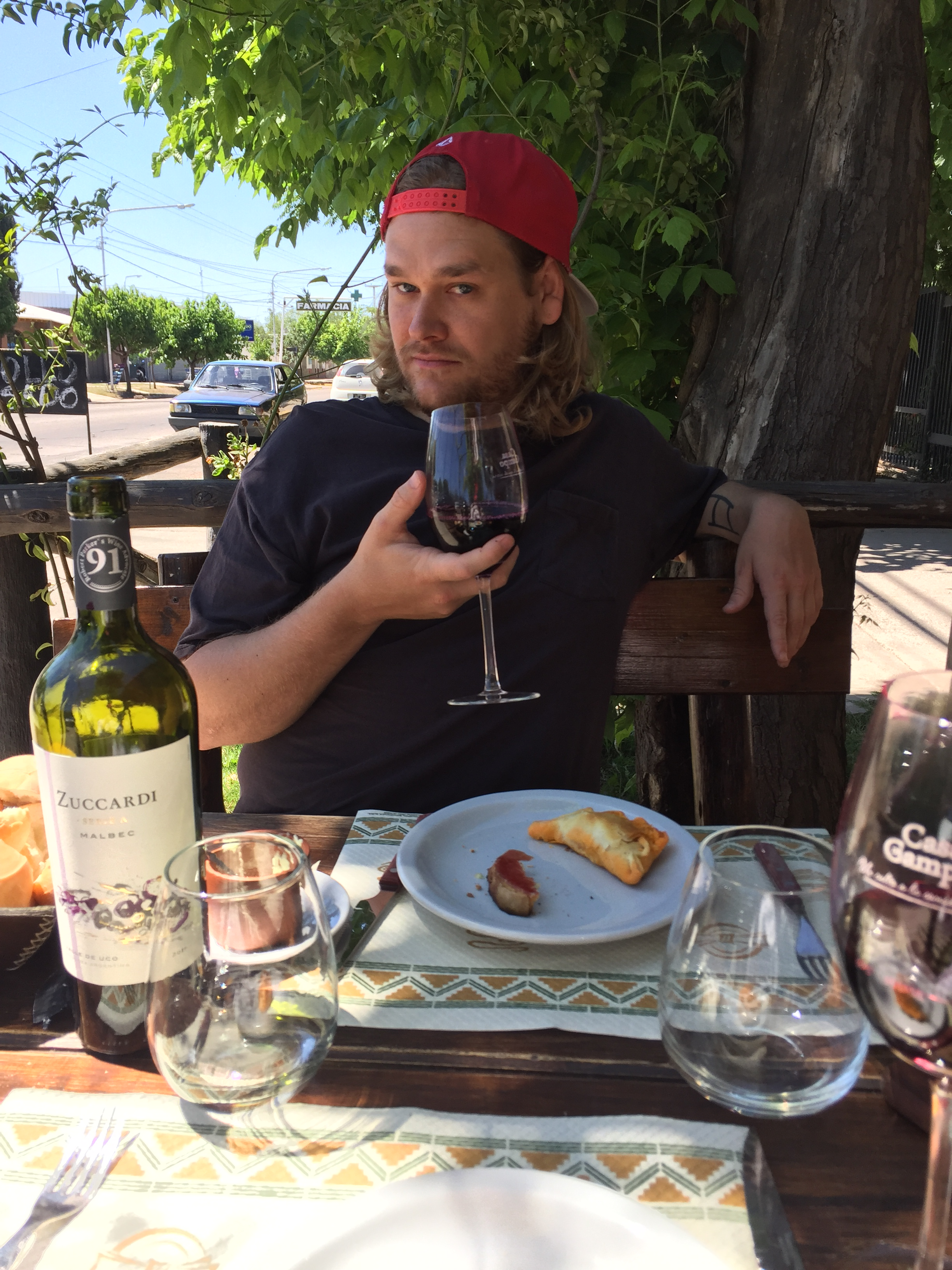 A man with long hair and a red hat sips on some red wine at a dinner table outside.