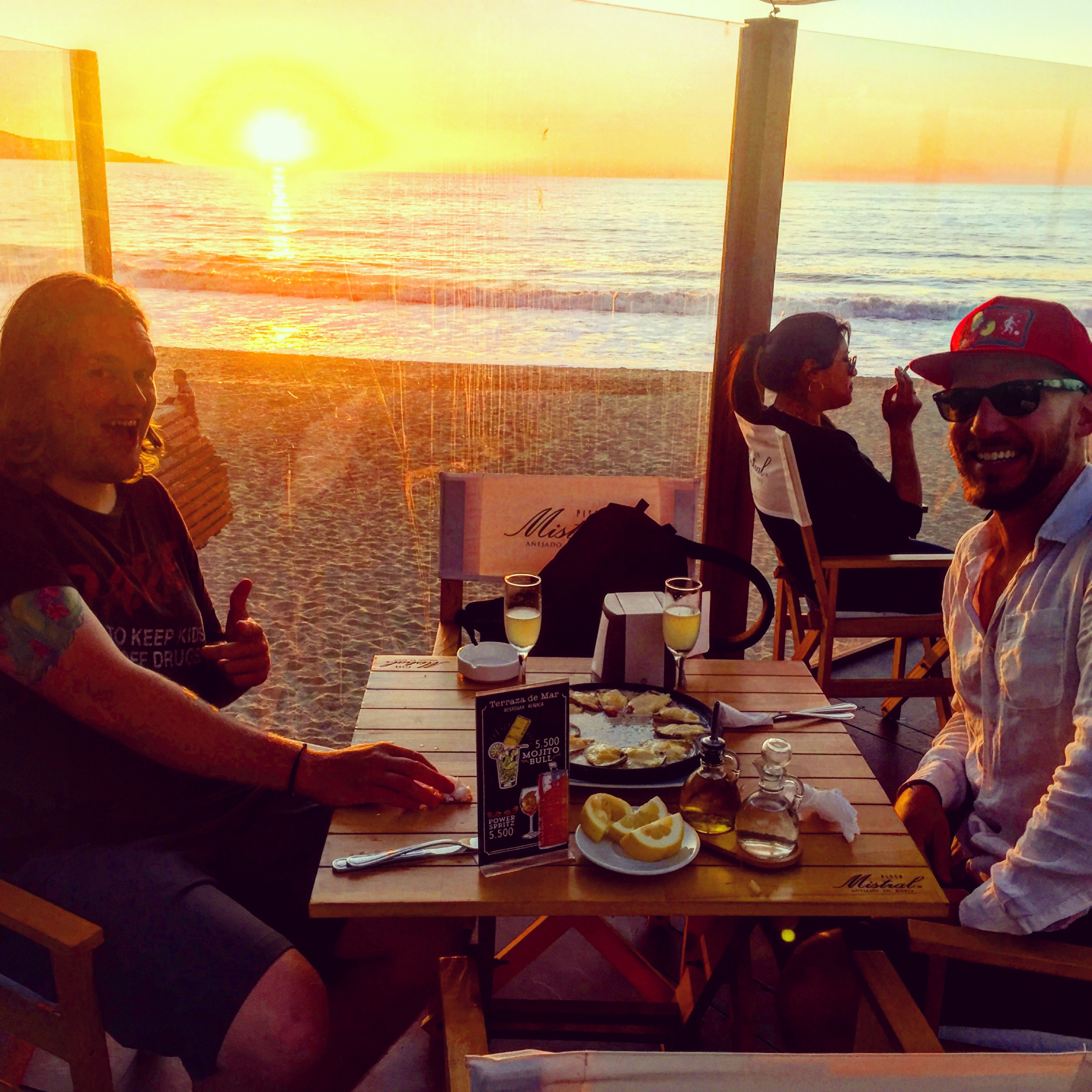 The gringos eat machas a la permesana and drink pisco sours on during the sunset on a beach in Reñaca Chile.